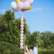 Happy young girl with big colorful latex balloons on seaside. Beauty Romantic Girl Outdoors. Woman  with long blond wavy hair  having fun on a lamppost on the background of blue sky. — Stock Photo #72635841