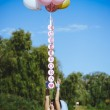 Happy young girl with big colorful latex balloons on seaside. Beauty Romantic Girl Outdoors. Woman  with long blond wavy hair  having fun on a lamppost on the background of blue sky. — Stock Photo #72635871