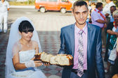 Groom holding slice of traditional wedding round loaf and bride — Stock Photo