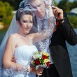 Bride And Groom Kissing Under Veil Holding Flower Bouquet In Hand — Stock Photo #72793223