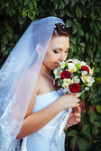 Portrait of beautiful young bride holding bright bouquet of flowers in hands. wedding celebration. reception. nature green background. woman alone outdoors in park — Stock Photo