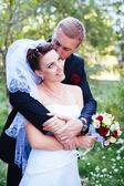 Brudparet på bröllopsdagen promenader utomhus på vår natur. Brudparet, lycklig nygift kvinna och man som omfattar i grön park. kärleksfull bröllop par utomhus. — Stockfoto