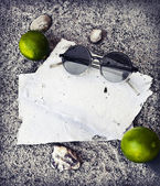 Papers, limes and sunglasses — Stock Photo