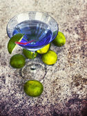 Cocktail glass with straw and limes — Stock Photo
