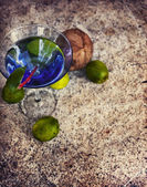 Cocktail glass, limes and coconut — Stock Photo