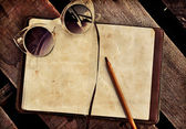 Sunglusses and copybook with pen — Stock Photo