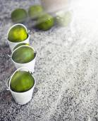 Little white buckets with limes — Stock Photo