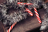 Candy canes wit holiday tinsel — Stock fotografie