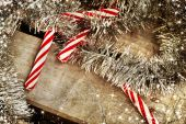 Candy canes wit holiday tinsel — Stock Photo