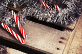 Candy canes wit holiday tinsel — Stockfoto