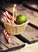 Christmas  candies and balls in basket — Stock Photo
