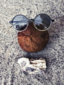 Sunglasses, coconut and shells — Stock Photo