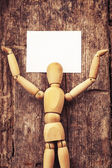 Wooden man holding  card — Stock Photo