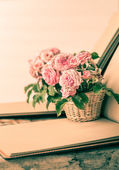 Pink roses with notepad  on wooden table — Stock Photo