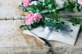 Pink roses with glasses on wooden table — Stock Photo