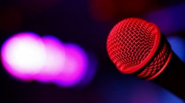 Microphone on stage with a colourful lights in background — Stock Video