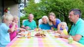 Big family of seven having meal outdoors — Stock Photo