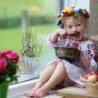 Cute Ukrainian girl eating from traditional plate — Stock Photo #52978957
