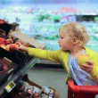 Cute little girl buying fruits in supermarket — Stock Photo #52979021