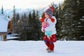 Adorable toddler girl playing in snowy park — Stock Photo