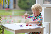Little girl drawing with brush indoors — Stock Photo