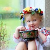 Cute Ukrainian girl eating from traditional plate — Stock Photo