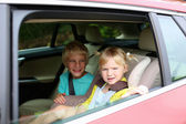 Brother and sister sitting safely in the car — Stock Photo
