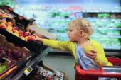 Cute little girl buying fruits in supermarket — Stok fotoğraf