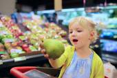 Cute little girl buying fruits in supermarket — Stockfoto