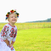 Little Ukrainian girl in traditional dress playing in the fields — Stock Photo