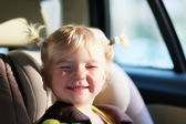 Funny little girl in car seat with safety belt — Stock Photo