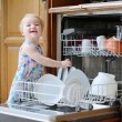 Little girl helping with dish washing machine — Stock Photo #53545109
