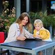 Mother and little daughter relaxing in outdoors cafe — Stock Photo #53545255