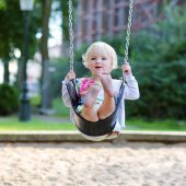 Little girl swinging at playground — Stock Photo