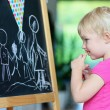 Preschooler girl drawing on black board — Stockfoto