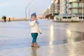 Lovely baby girl walking on beach promenade — Stock Photo