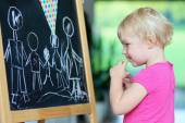 Preschooler girl drawing on black board — Stock Photo