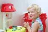 Preschooler girl playing with toy kitchen — Foto de Stock