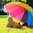 Little girl walking with colourful umbrella — Stock Photo #54522071