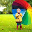 Little girl walking with colourful umbrella — Stock Photo #54522099