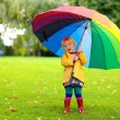 Little girl walking with colourful umbrella — Stock Photo #54522101