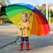 Little girl walking with colourful umbrella — Stock Photo #54522103