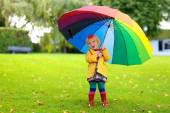 Little girl walking with colourful umbrella — Stock Photo