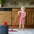 Lovely preschooler girl mopping the floor in kitchen — Stock Photo #54859783