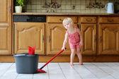 Lovely preschooler girl mopping the floor in kitchen — Stock Photo