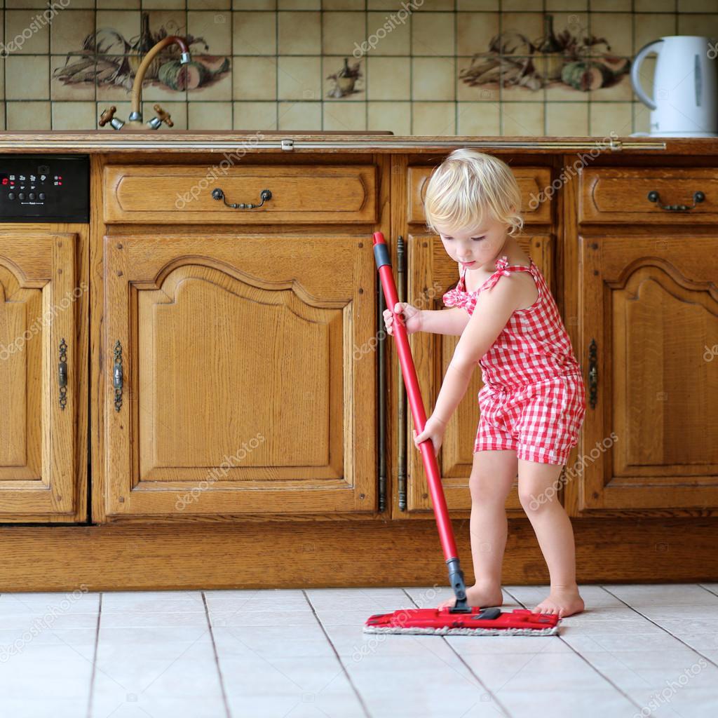 Mooie peuter meisje dweilen de vloer in de keuken — stockfoto ...