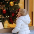 Little girl looking at shop window during christmas time — Stock Photo #55742789
