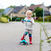Little girl riding on push scooter on street — Stock Photo