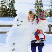Mother and daughter playing in winter park — Stock Photo