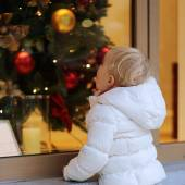 Little girl looking at shop window during christmas time — 图库照片